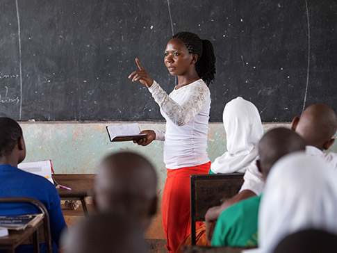 Alumna Learner Guide leading a class of secondary school students in Tanzania